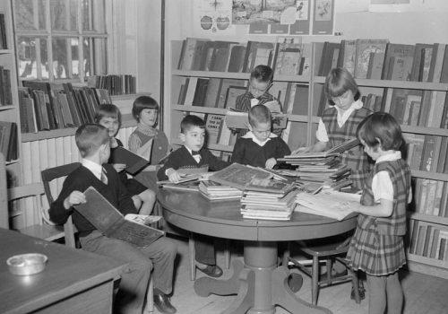 Des enfants lisent autour d'une table à la bibliothèque de Elizabeth Ballantyne School de la rue Northview à Montréal-Ouest, 1960, Bibliothèque et Archives nationales du Québec, P48,S1,P22899.